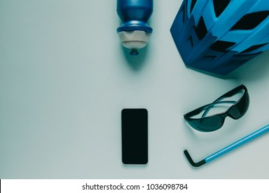 Cycling accessories on blue background, and gps route on mobile