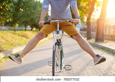 Cycling around. Close up of hipster man riding bicycle with his legs in the air