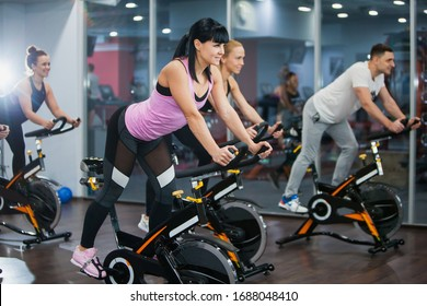 Cycling class in fitness club, group of fit people spinning on cardio machine. Man and women do sports exercises at gym fat burning class. Active lifestyle, health care and body training concept
