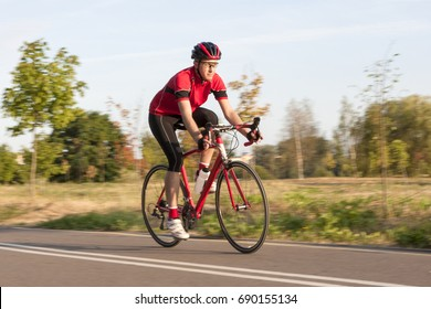 Cycling Concepts. Professional Male Cyclist in Racing Outfit During a Ride on Bike Outdoors. Panning Technique Used. Horizontal Image Composition