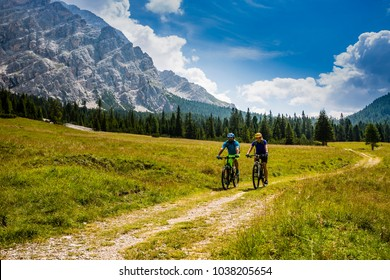 Cycling couple with bikes on track, Cortina d'Ampezzo, Dolomites, Italy