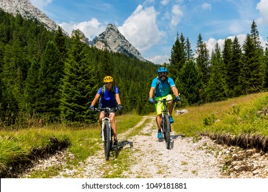 Cycling couple on MTB track, Cortina d'Ampezzo, Dolomites, Italy
