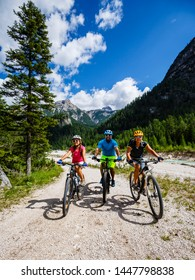 Cycling family riding on bikes in Dolomites mountains landscape. Cycling MTB enduro trail track. Outdoor sport activity.