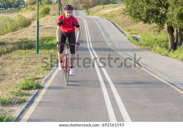 Cycling Ideas. Portrait of Professional Male Cyclist Doing Uphill on Road Bike. Fully Equipped in Professional Outfit. Horizontal Shot