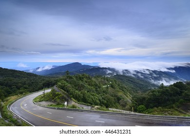 Cycling mountain road. Misty mountain road in high mountains. High mountain road is being covered with fog. Cloudy sky with mountain road view in sunrise.