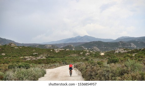 Cycling. Offroad Cycling in Agriates Desert, Corsica, France. a red shirt cyclist, Dusty road, Rocky road, Mediterranean Vegetation. Mountains, Daylight. Cloudy sky. Courage for the Journey.