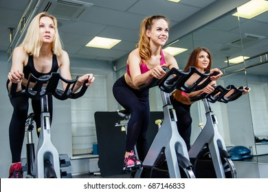 Cycling on exercise bikes. Three attractive young women in sports clothing exercising on gym bicycles