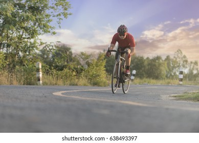 Cycling on road. Asian man is cycling road bike with sunset.