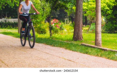 Cycling outdoor - Biker girl exercise in the park, woman fitness, healty lifestyle