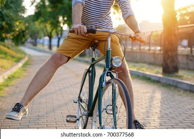 Cycling in the park. Close up of man riding bike