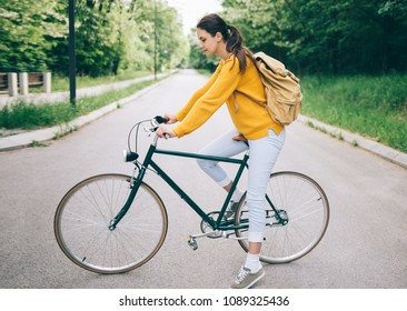 Cycling in the park. Side view of student girl with bicycle