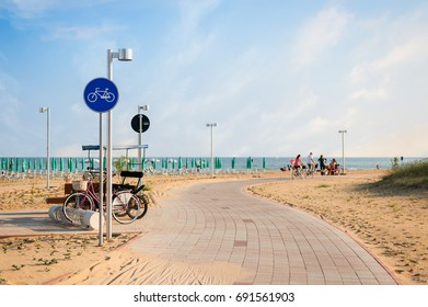 Cycling path with signal near beach on blue sky. Bibione,Italy
