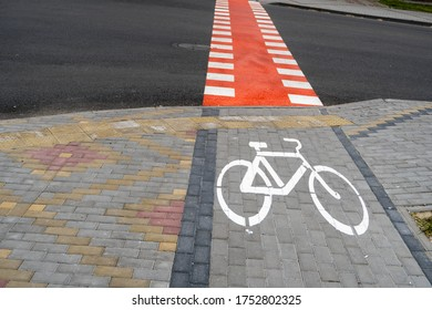 Cycling path with a symbol of bike on a ground through avtomobile road. Bike path in a modern city.