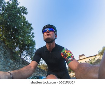 Cycling pov selfie. Young adult cyclist taking a selfie portrait while training on a racing bicycle on a sunny spring or summer afternoon