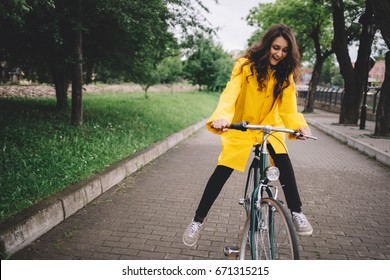 Cycling in the rain. Cheerful young woman riding bicycle and wearing raincoat