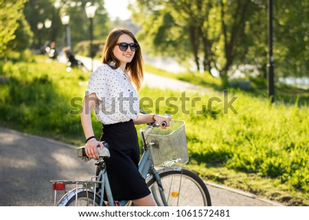 Cycling relax leisure outdoor nature concept. Girl with bike. Young elegant lady in park taking a walk leading bicycle with her.