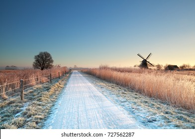 cycling road and windmill in Dutch countryside during winter