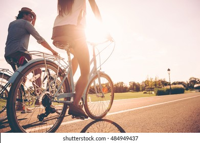 Cycling together. Low angle view of young people riding bicycles along a road together
