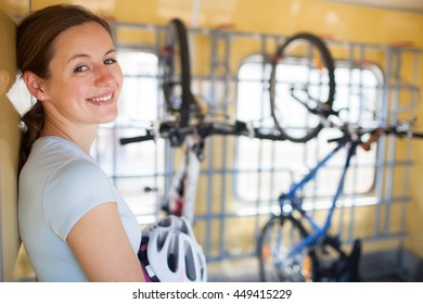 Cycling tourism: young woman traveling by train with her bike