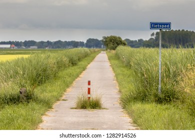 Cycling track or fietspad through green flat open polder landscape in Groningen province Netherlands