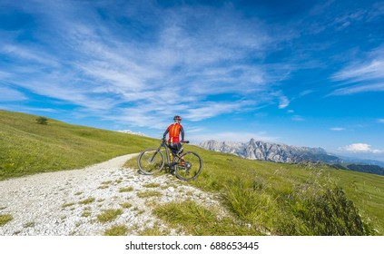 Cycling in Trentino Alto Adige on summer season. Man in mountiain bike Enjoying a landscape in Dolomites region mountains.