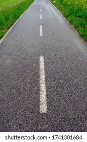 Cycling way along green fields with road marking