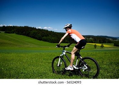 A cycling woman in front of forest