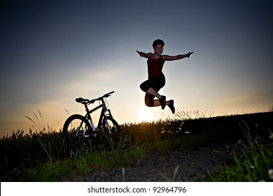 A cycling woman jumps and cheers in front of rural landscape