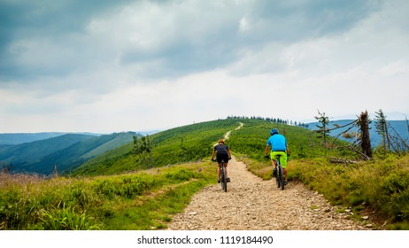 Cycling woman and man at Beskidy mountains forest landscape. Couple riding MTB enduro track. Outdoor sport activity.