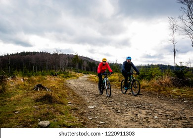 Cycling woman and man at Beskidy mountains autumn forest landscape. Couple riding MTB enduro track. Outdoor sport activity.