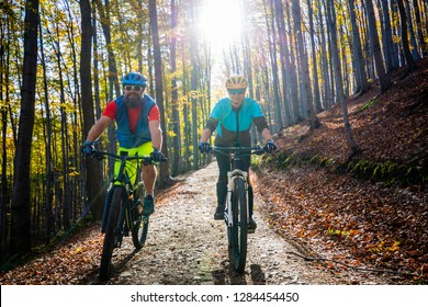 Cycling woman and man at Beskidy mountains spring forest landscape. Couple riding MTB enduro track. Outdoor sport activity.