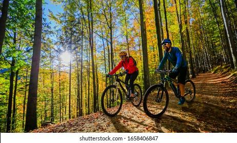 Radfahrerin und Mann, die auf dem Rad in der Waldlandschaft des Sonnenuntergangs reiten. Mehrere Radfahrer MTB Enduro-Flussweg. Sportliche Aktivitäten im Freien.