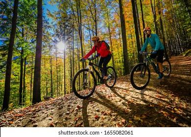 Radfahrerinnen und Radfahrer bei Sonnenuntergang in der Waldlandschaft der Berge. Mehrere Radfahrer MTB Enduro-Flussweg. Sportliche Aktivitäten im Freien.