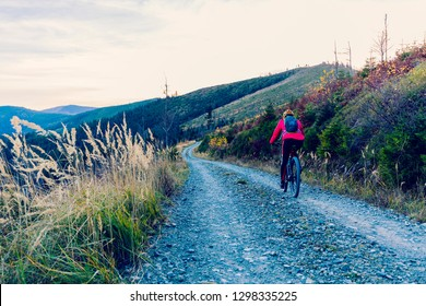 Cycling woman riding on bike in autumn mountains forest landscape. Woman cycling MTB flow trail track. Outdoor sport activity.