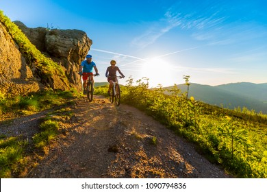 Cycling women and man riding on bikes at sunset mountains forest landscape. Couple cycling MTB enduro flow trail track. Outdoor sport activity.
