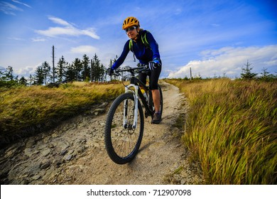 Cycling women riding on bike in autumn mountains forest landscape. Woman cycling MTB flow trail track. Outdoor sport activity.