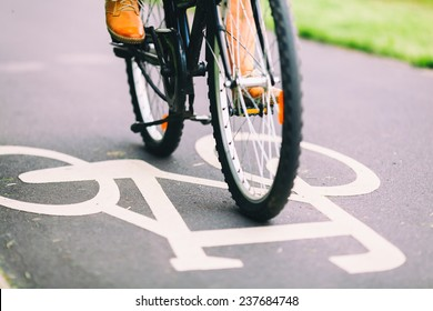 Cycling to work. City bike sign on asphalt bikepath man cycling on road, colorful vintage light on street, commuting to work on bicycle in urban environment