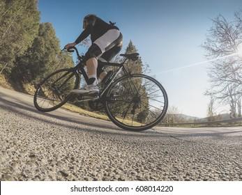 Cycling. Young adult athlete riding a racing bicycle on a mountain road on a spring afternoon