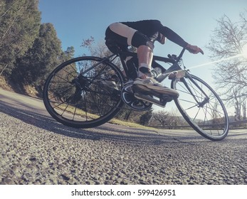 Cycling. Young adult man riding a racing bicycle on a sunny spring afternoon.