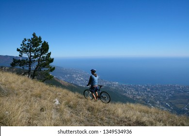 Cyclist admires from the top views of Yalta, Crimea, Russia.