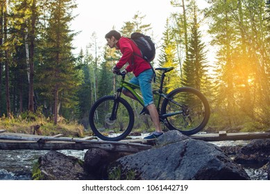 Cyclist with a backpack on a mountain bike goes through the river bridge in the forest at sunset. The concept of an active lifestyle with nature