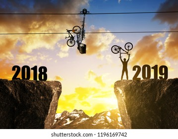 Cyclist with bicycle on rock at sunset. Forward to the New Year 2019.