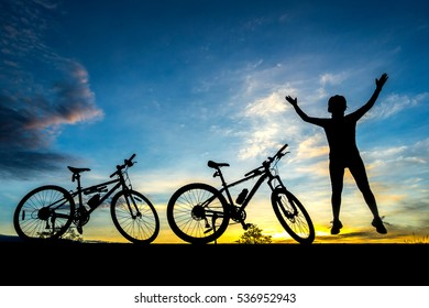 cyclist and Bicycle silhouettes on the dark background of sunsets