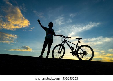 cyclist and Bicycle silhouettes on the dark background of sunsets.C