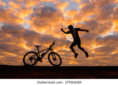 cyclist and Bicycle silhouettes on the dark background of sunrise and  dark clouds.