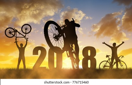 Cyclist with bicycle at sunset. Forward to the New Year 2018