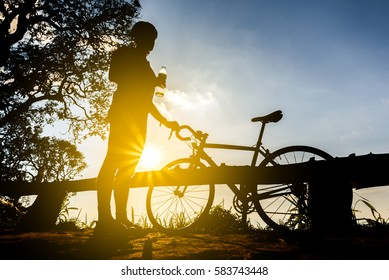 cyclist with a bike silhouette on sunset sky background