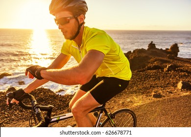 Cyclist biking looking at smartwatch while riding road bike. Athlete biker using activity tracker gps fitness watch on biking workout in sunset. Sports man using his watch app for fitness tracking.