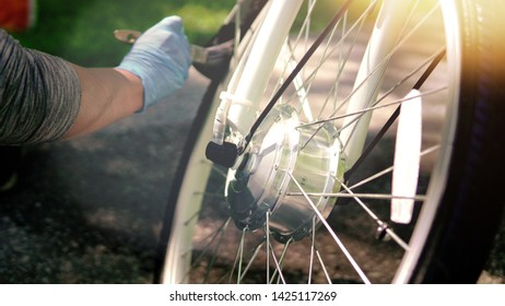 Cyclist in blue gloves is cleaning the electric bicycle motor wheel tire with the brush, outside, bright sunny summer day. Light leaks. Focus at the motor.  Rider take care of the ebike.