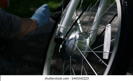 Cyclist in blue gloves is cleaning the electric bicycle motor wheel tire with the brush, outside in the summer day. Focus at the motor.  Rider take care of the sport e bike wheel with motor.